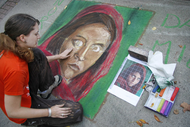 Kim Roseberry of Biddeford uses chalk to re-create the image of an Afghan girl during the Chalk on the Walk event in Biddeford on Saturday. The Afghan girl was photographed by National Geographic photographer Steve McCurry in 1984.