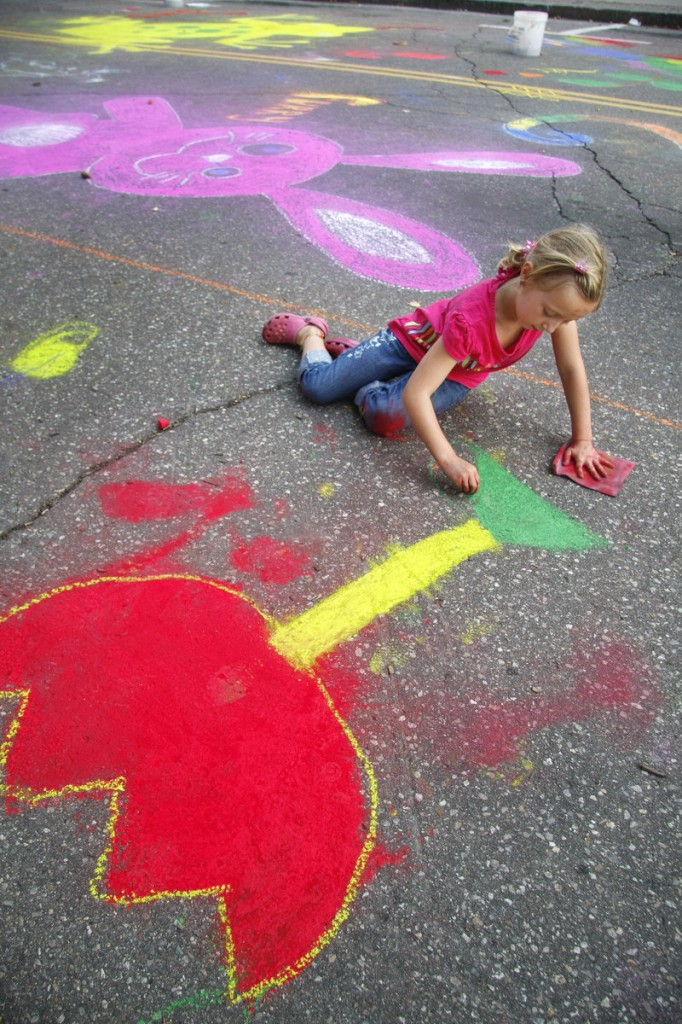 Madison Paquette, 7, adds a flower to the community mural on Adams Street during Saturday s Chalk on the Walk sponsored by Heart of Biddeford.