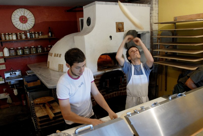 Mihai Dobre and Gabor Gergely make pizzas in the kitchen of Paolina's Way.