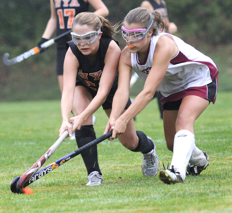 Jen Brown, left, of North Yarmouth Academy battles with Jenny Breau of Freeport during NYA s 5-0 field hockey victory Monday.