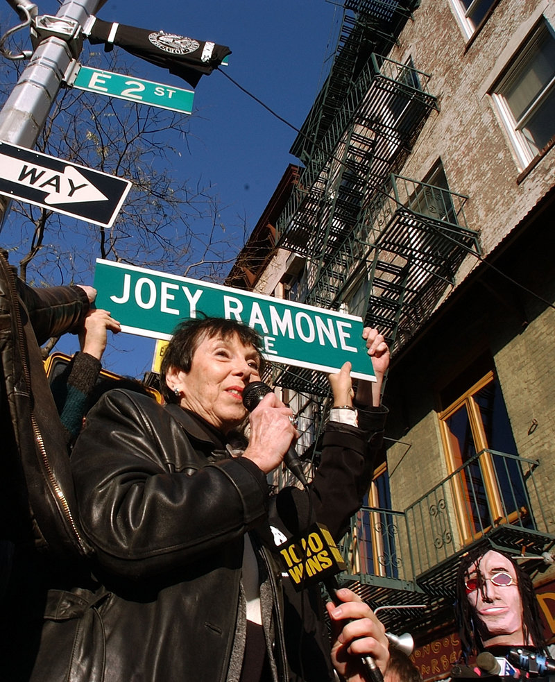 In this 2003 file photo, Charlotte Lesher, the mother of late singer Joey Ramone, holds a sign that names the corner of Bowery and 2nd Street in New York as Joey Ramone Place.