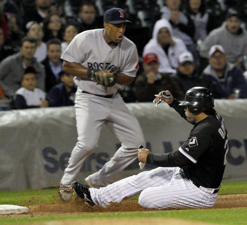 Carlos Quentin of the White Sox slides under the throw to Boston third baseman Adrian Beltre, advancing on a double by Alexei Ramirez, but the Red Sox picked up a 6-1 win at Chicago.