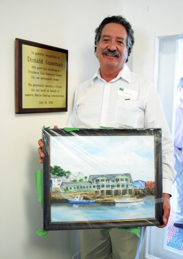 S. Donald Sussman shows off a painting of the new home for the Penobscot East Resource Center. Sussman received the painting as a gift after donating the restored waterfront building to the group.