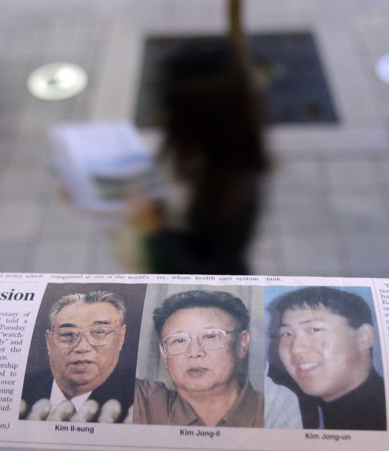 A South Korean newspaper with photos of North Korean leader Kim Jong Il, center, his late father, left, and a photo said by South Korean media to be of Kim's youngest son, Kim Jong Un, is seen on a Seoul newsstand Tuesday.