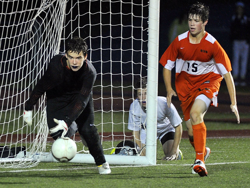 Sam Torres of Yarmouth looks through the net Tuesday night to see if his pass across the front of the goal finds a teammate. North Yarmouth Academy goalie Ryan Salerno chases the ball as Forrest Milburn of the Panthers moves in. Yarmouth came away with a 1-0 victory.