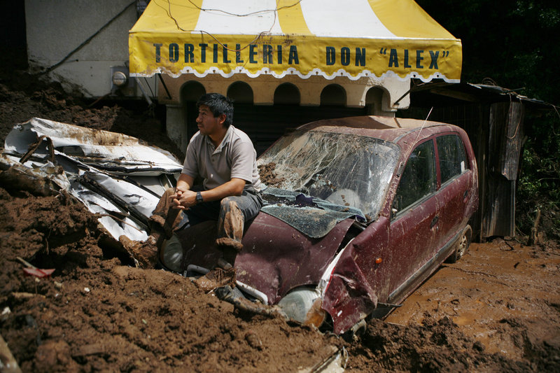 A man rests on a damaged vehicle Wednesday in the aftermath of a landslide in Santa Maria de Tlahuitoltepec in Oaxaca state, Mexico. The government delivered blankets and other supplies to survivors and others who fled their unstable homes for fear of more mudslides.