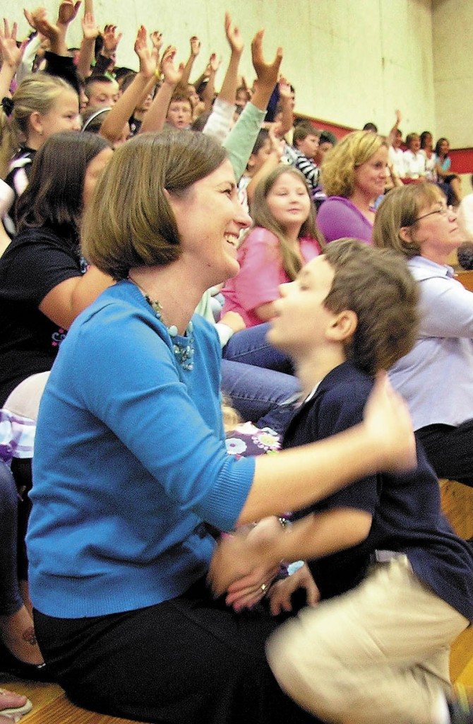 HELPING HANDS: Shelly Moody, a teacher at Williams Elementary School in Oakland, holds onto her 5-year-old son, Jacob, Friday morning as she is announced as the 2011 Maine Teacher of the Year. The school assembly was advertised as a gathering about anti-bullying to keep it a surprise. In the background, students, teachers and parents raised their hands when asked whether they thought the assembly was about something else.