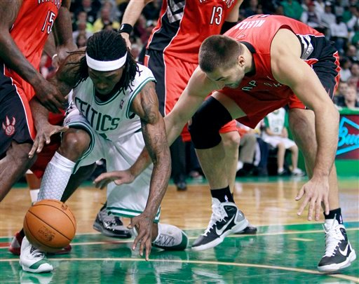 Boston Celtics' Marquis Daniels, left, battles Toronto Raptors' Linas Kleiza for the loose ball in the first quarter of a preseason NBA basketball game on Sunday in Boston. The Celtics won 91-87.