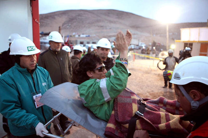 In this photo released by the Chilean government, miner Claudio Yanez applauds as he is carried away in a stretcher after being rescued early today.