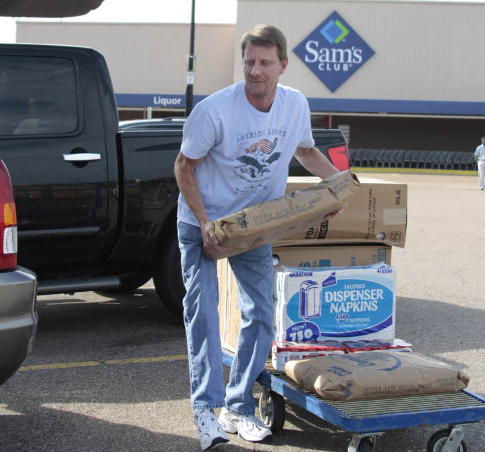Bryan Daniels loads supplies into his SUV at Sam's Club in Jackson, Miss., recently. Economists think consumers will spend at a slightly slower pace through the rest of this year.