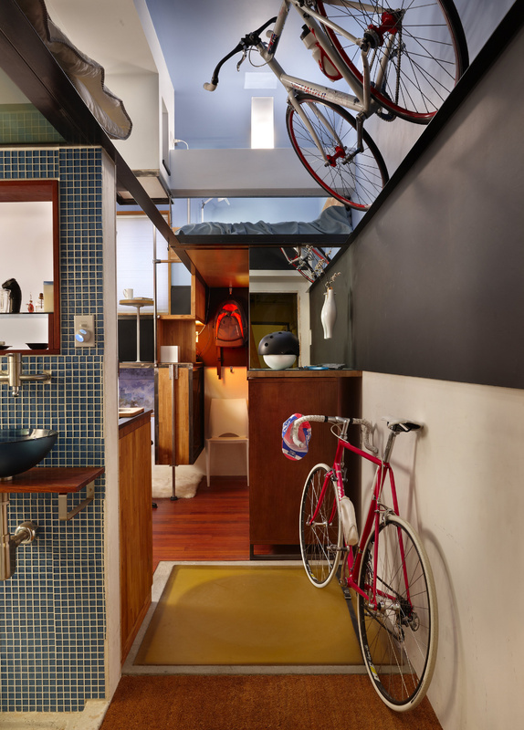 In the tiny apartment of Steve Sauer, one bike is tethered to the ceiling for storage. Steam heat comes from the building's system. The ventilation chimney runs across Sauer's ceiling, and was easy to pipe into.