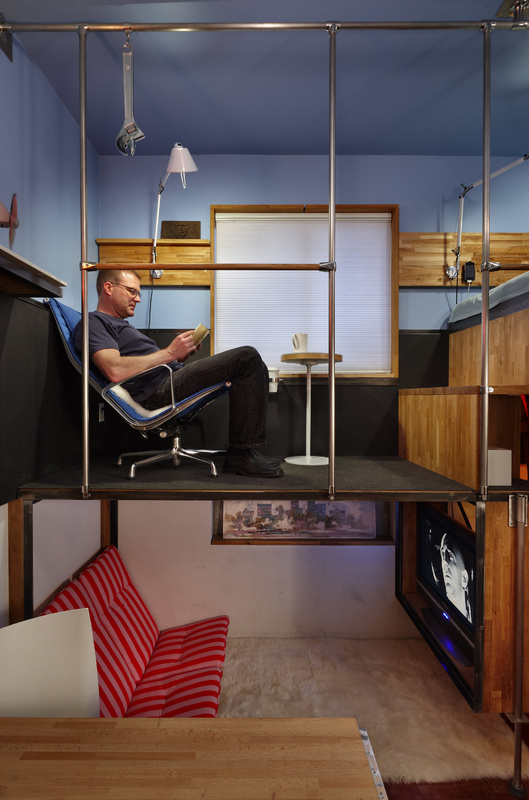 Steve Sauer relaxes in the cafe area of his 182-square-foot condo.