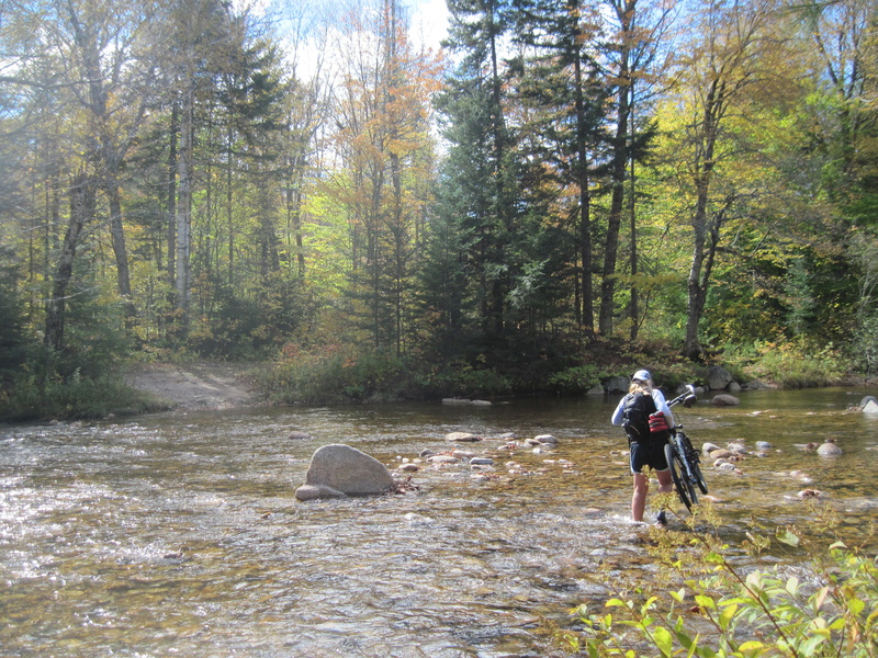Kate Hossler carries her bike across the shallow but cold Swift River to reach the trail on the other side.