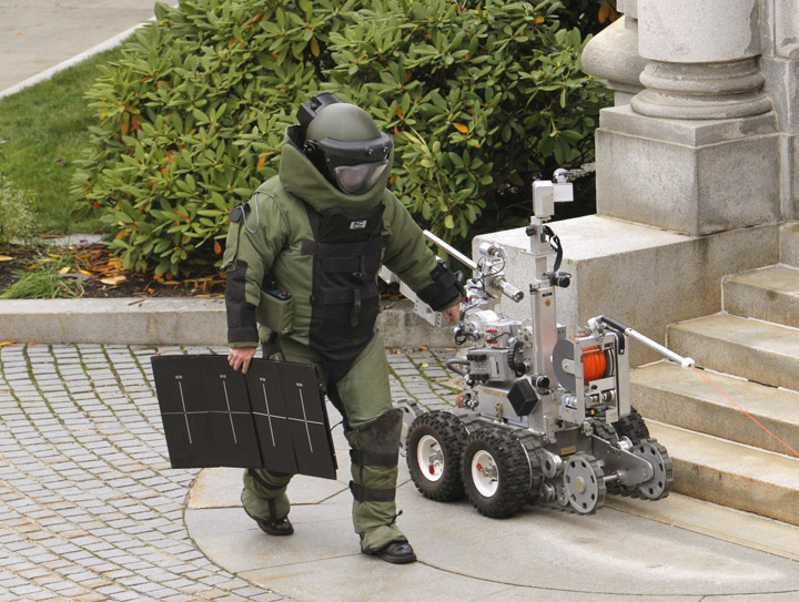 Portland police bomb specialist Jay Twomey carries a piece of X-ray equipment away from a bush by the Edward T. Gignoux United States Courthouse where a suspicious package was spotted early this morning.