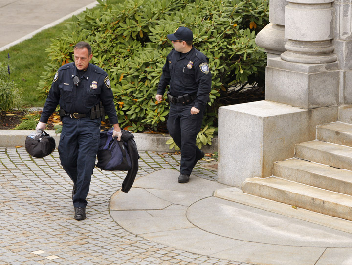 Federal courthouse security personnel carry a duffel bag and backpack away from the entrance to the federal courthouse in Portland today. Police closed down Federal Street for five hours as they tried to determine what was in the package.