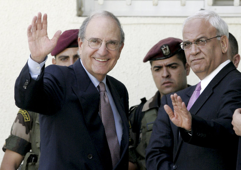 U.S. envoy George Mitchell, left, and chief Palestinian negotiator Saeb Erekat, right, wave before a meeting Thursday with Palestinian President Mahmoud Abbas in the West Bank city of Ramallah. An Abbas aide says peace talks cannot continue without an Israeli settlement freeze.