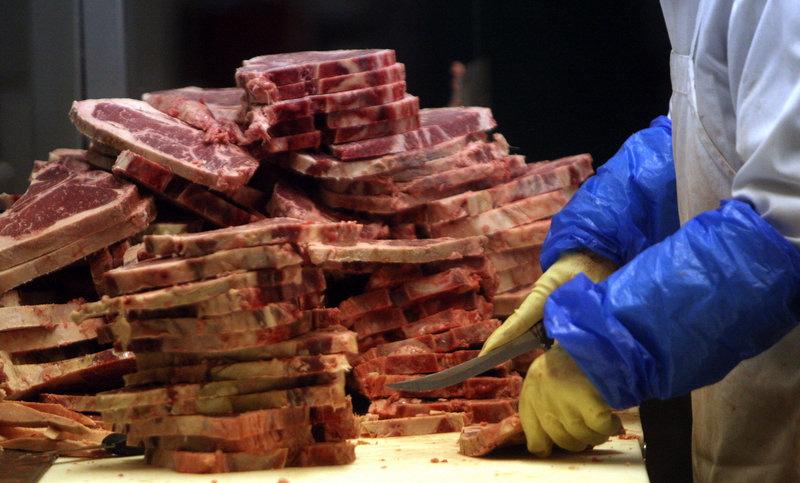 A worker slices up meat at a Chicago meat company. The costs not calculated in the direct consumer price of meat touch on such issues as health, taxpayer expense, the environment and animal welfare.
