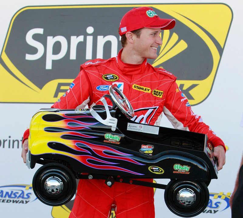Kasey Kahne holds a peddle car, his reward for winning the pole position for Sunday's Sprint Cup race at Kansas Speedway.