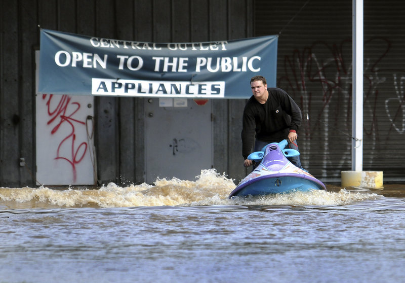 Matt Mitsdarfer rides his personal watercraft in a flooded Stanton, Del., parking lot Friday. Parts of the East Coast got up to 6 inches of rain in hours from a storm that was blamed for five deaths in North Carolina and one in Pennsylvania.