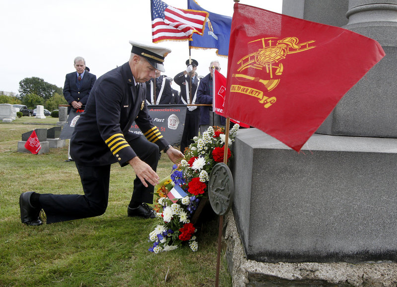 Robert Wassick, deputy chief of the Portland Fire Department, lays a wreath beside the Portland Veteran Firemen's Association Monument on Sunday during a ceremony in Forest City Cemetery to honor lost firefighters from Portland and South Portland.