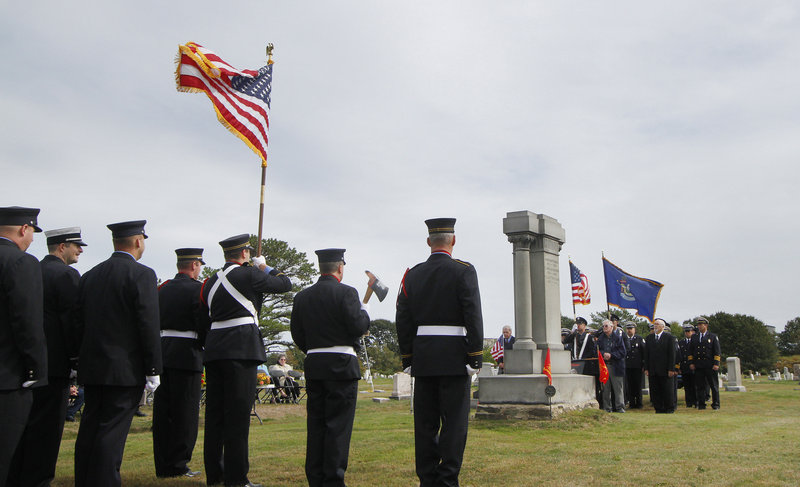 Portland and South Portland firefighters line up around the Portland Veteran Firemen's Association Monument on Sunday. More than 60 people turned out to honor fallen firefighters.