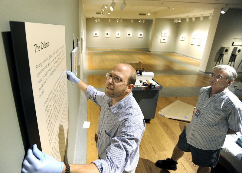 Ray Routhier, left, hangs a panel at the Portland Museum of Art under the direction of preparator Greg Welch as Welch sets up a photography exhibit. Welch has held this job for 35 years.