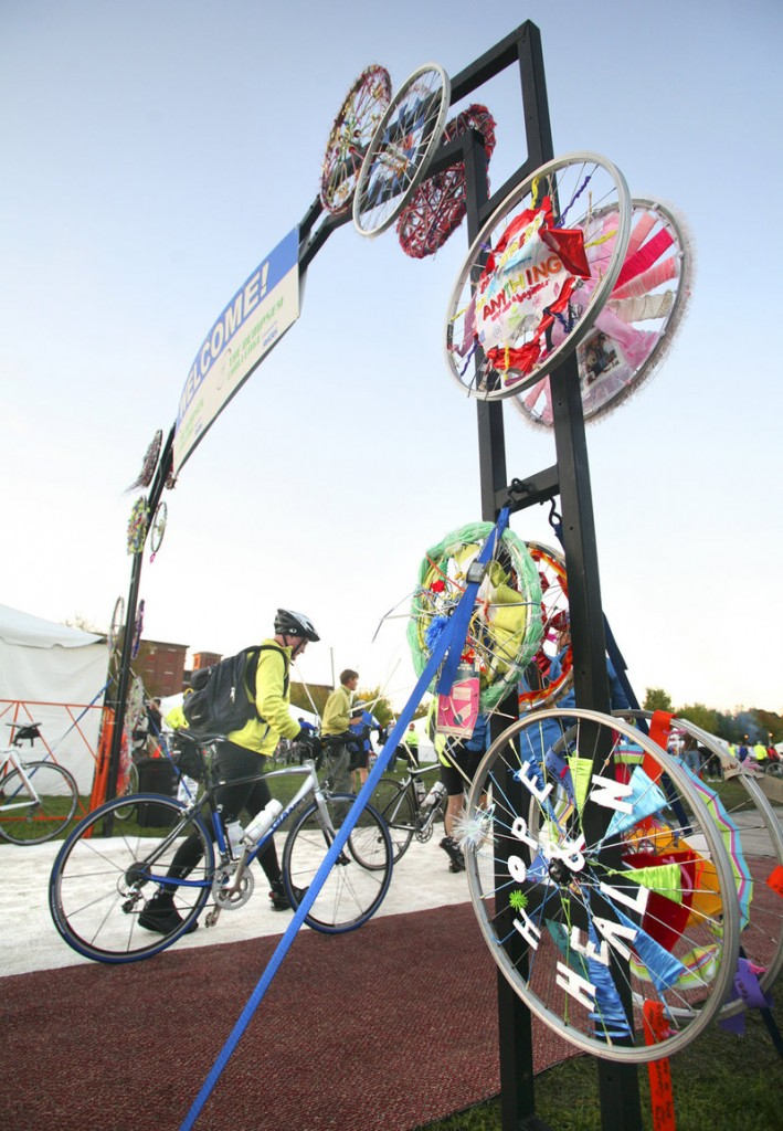 Bicycle rims decorate the entrance as cyclists arrive at Simard-Payne Police Memorial Park to register before the start of the Dempsey Challenge in Lewiston on Sunday.