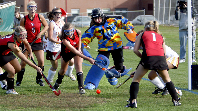 Jaclyn Salevsky, center, of South Portland swats the ball toward the goal as Thornton Academy goalie Abbey Siulinski moves out to block the shot Monday in Saco. Thornton got three second-half goals for a 4-2 victory.