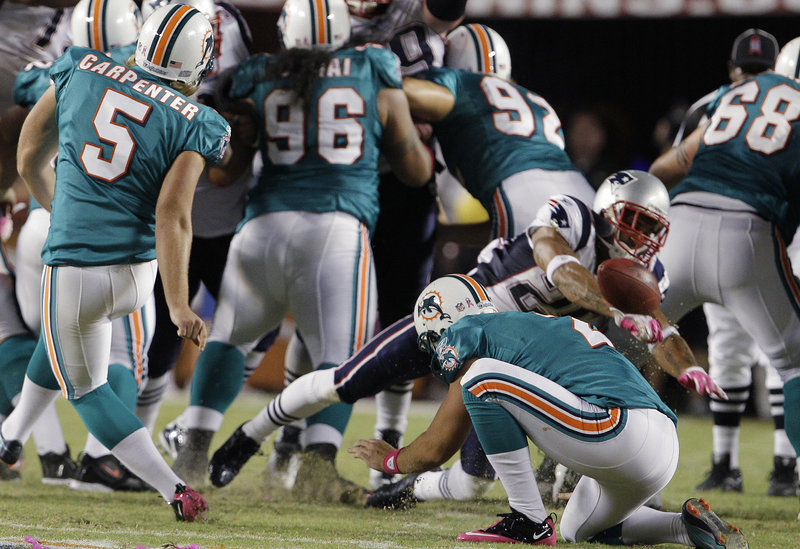 New England's Patrick Chung gets the jump on Miami kicker Dan Carpenter and holder Brandon Fields to block an attempted field goal during the second half Monday night in Miami. The Patriots scored 35 second-half points to pull away from the Dolphins.