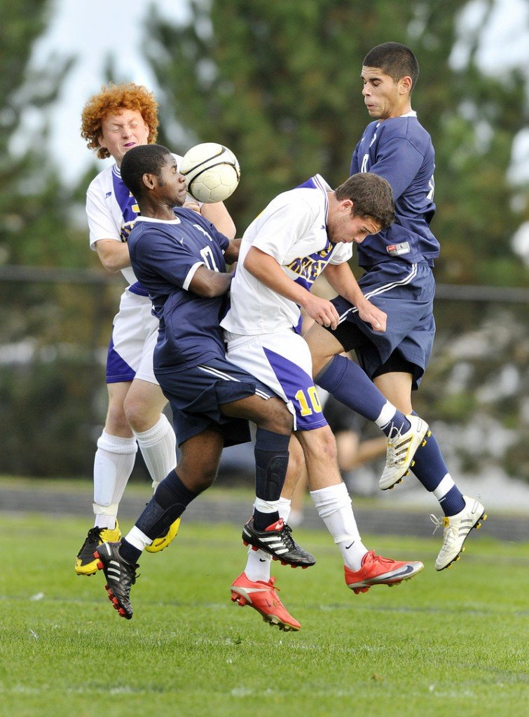 Ralph Houanche, front left, of Portland collides with Nicholas Melville of Cheverus as they battle Cheverus' Parker Doyon and Portland's Fazal Nabi for control of the ball.