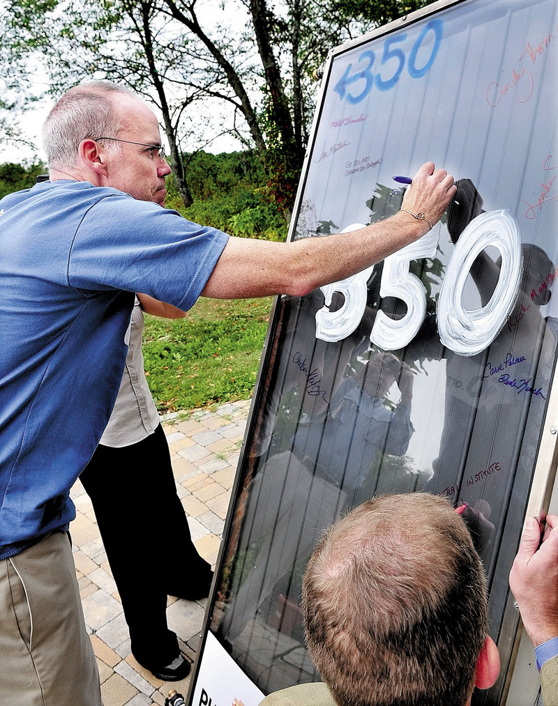 Environmental activist Bill McKibben signs a solar panel at Maine's Unity College in Unity last month. McKibben and students took the panel, which was once installed atop the White House, back to Washington to argue for reinstalling solar panels on the White House roof.