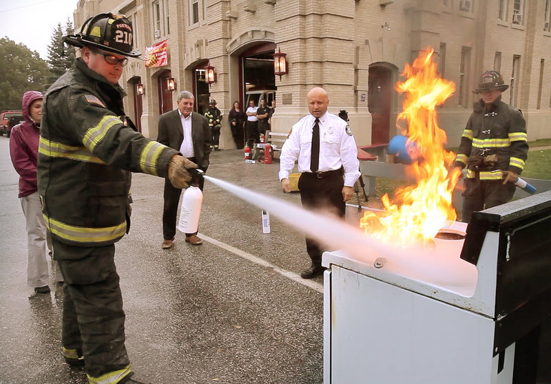 As part of Fire Prevention Week, firefighter Randy Stewart demonstrates how to use a fire extinguisher to put out a stove fire at Central Fire Station in Portland on Wednesday.