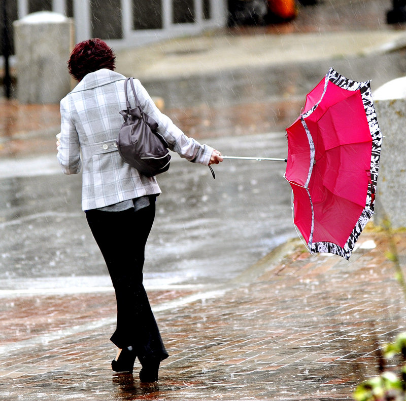 Amy Baum of Waterboro hangs on to her inside-out umbrella as she crosses Free Street in Portland on Wednesday. A soaking rain and gusting winds invaded Maine as a storm system made its way north.