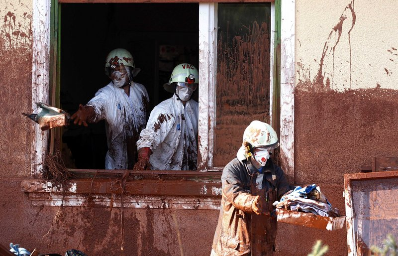 """Caked with sludge, firefighters clean a house flooded by toxic mud in Kolontar, Hungary, on Thursday. When he visited the village on Thursday, Prime Minister Viktor Orban described the reservoir break as an unparalled disaster in the nation's history, saying """"This is so irresponsible that it is impossible to find words."""""""