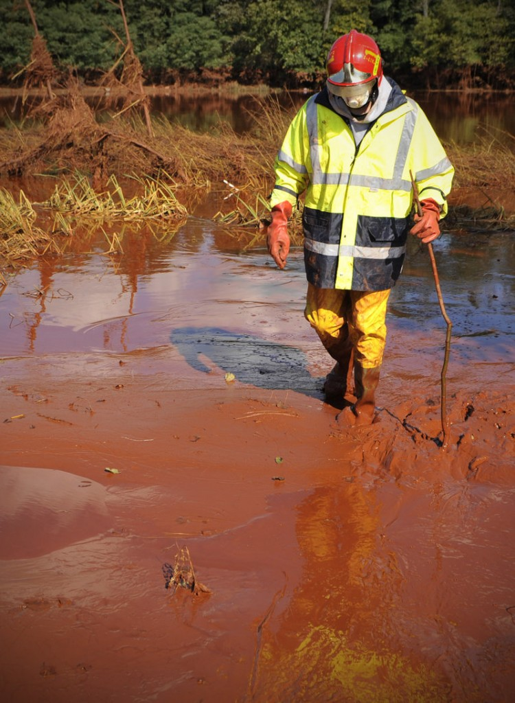 A Hungarian firefighter wades through toxic red sludge that burst out of a Hungarian factory's reservoir and inundated three villages before reaching the Danube River on Thursday.