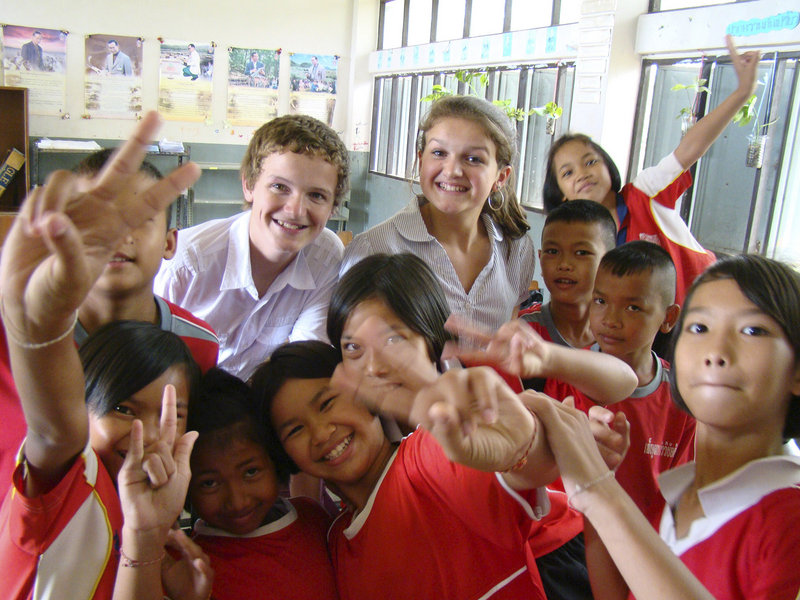 Logan, left, and Jackson Marshall sit in for a group picture with children at a school in Thailand, where they and their parents taught English – one of several working stays the family made as part of an international experience this year.