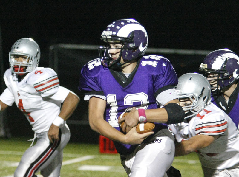 Deering quarterback Jamie Ross has a firm grip on the ball as he gets pressure from South Portland s Stephen Hodge, right, and Jacob Stanley, left, in first-half action of the Rams 35-0 win Friday night at Deering.