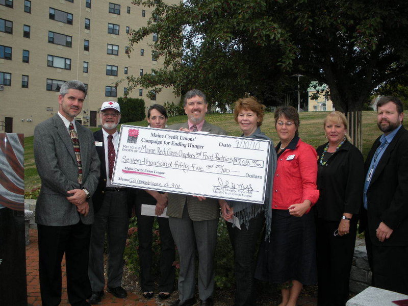 Jon Paradise, the Maine Credit Union League s public affairs manager, flanked at Portland s 9/11 Memorial by representatives by Maine s five Red Cross chapters and food pantries in each chapter s service area, holds a big check representing the total amount presented by the league to the groups.