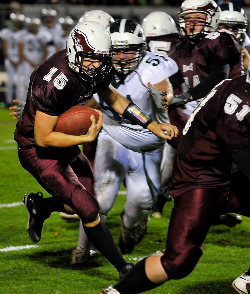 Cody Laberge of Windham follows lead blocker Shawn Francoeur while Bonny Eagle's Nick Cawood moves in Friday night during a Class A football game at Windham. Bonny Eagle won, 21-19.