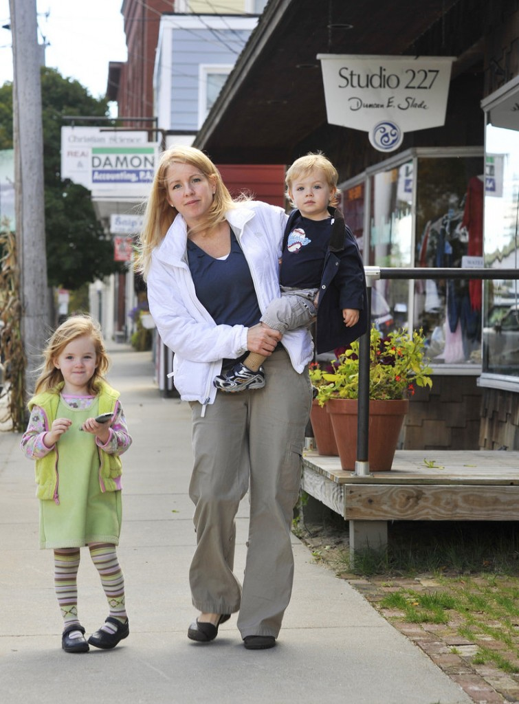 """Kerry Hewson, with her children Lauren, 3, and Grady, 2, on Main Street in Norway. Hewson, who moved to town about four months ago from suburban Detroit, believes a casino represents """"cheap thrills"""" and is not right for the area."""