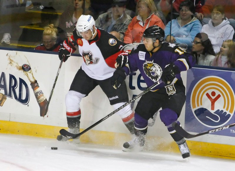 T.J. Brennan, left, of the Portland Pirates competes for the puck along the boards with Felix Schutz of the Manchester Monarchs during the first period of Portland's 6-5 victory. The American Hockey League season opened Saturday night.