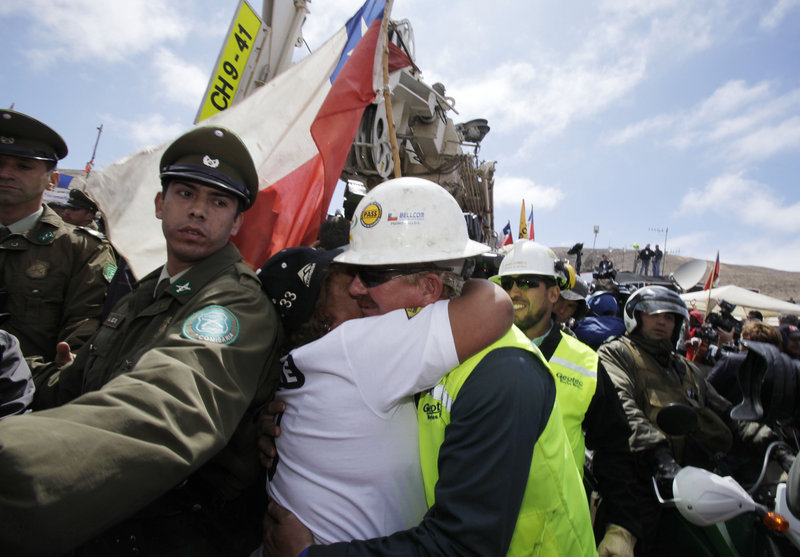 Maria Segovia, sister of trapped miner Dario Segovia, embraces Jeff Hart, operator of the T-130 drilling machine being used to reach 33 trapped miners, as the drill leaves the San Jose mine Monday near Copiapo, Chile.