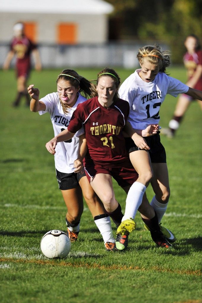 Megan Crepeau, left, and Olivia Jones of Biddeford put the squeeze on Thornton Academy's Kaitlyn Hall during their SMAA soccer game Monday at Biddeford.