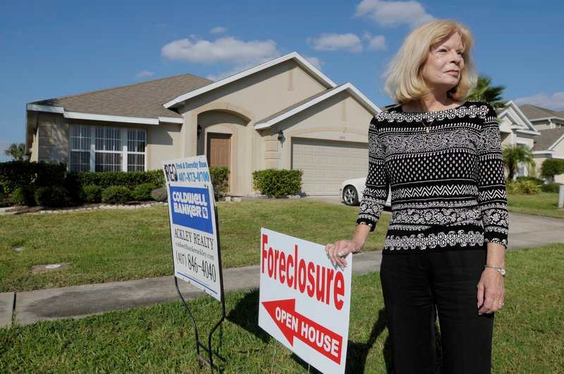 Realtor Dorothy Buse is seen in front of a foreclosed Kissimmee, Fla., home Wednesday. An announcement of an inquiry by up to 40 state attorneys general into banks' use of flawed foreclosure paperwork could come as soon as today.
