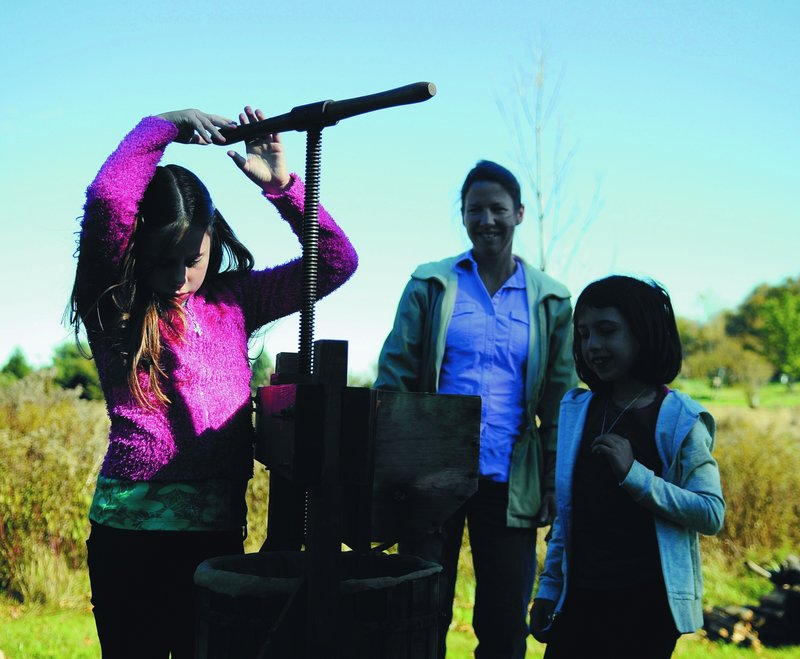 Geneva Smith, 9, turns the apple press Monday at the Viles Arboretum in Augusta, as she learns to make cider with her mother, Jodi, and sister, Leah, 7.