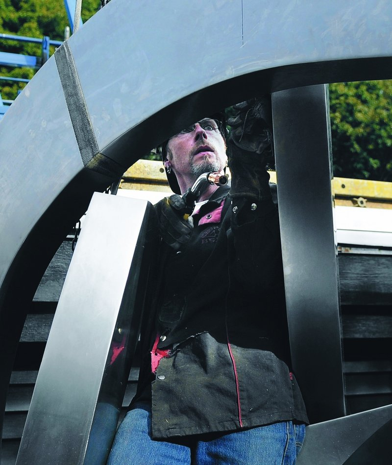"Robert Lash inspects a seam he welded near the top of the ""Rising"" sculpture at his studio and home in Gardiner."