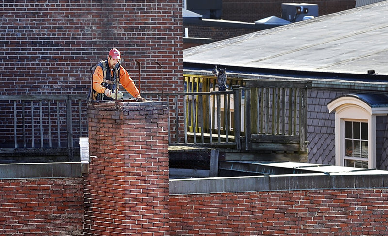Scott Cook, a mason for South Portland-based Team Masonry, works in the sun as he repoints an old chimney on the roof of a building on Free Street on Tuesday. It should remain sunny and in the upper 50s today and Thursday before taking a rainy turn Friday and Saturday.