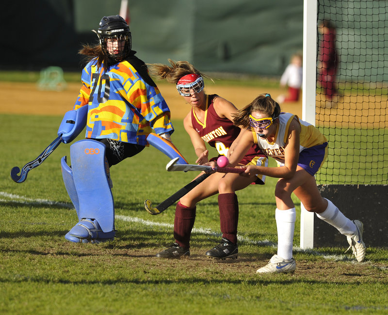 Emily Rodrigue, right, of Cheverus tries to redirect a pass in front of the net while defended by Thornton Academy s Ashley Gaudette and goalie Abbey Siulinski, who made nine saves for her ninth shutout as the Trojans won, 2-0.