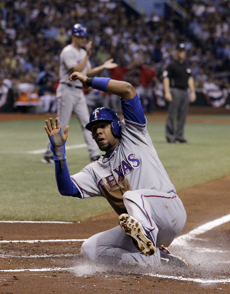 Elvis Andrus of the Texas Rangers scores in the first inning Tuesday night – the start of a 5-1 victory that eliminated the Tampa Bay Rays from the American League playoffs.