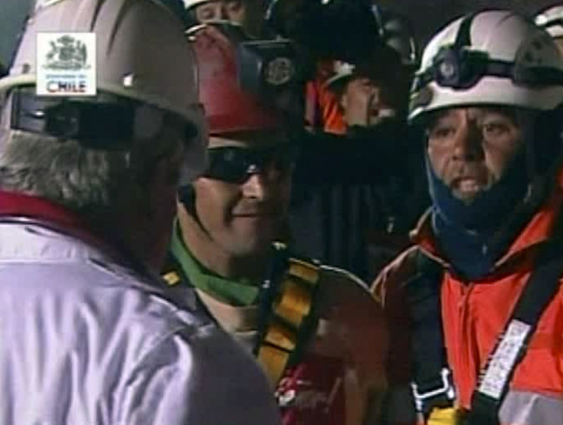 Florencio Avalos, center, the first miner to be rescued, steps from the capsule late Tuesday.